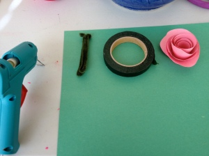 Hot Glue gun, green paper, finished rose, pipe cleaner, and flower tape